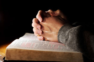 Hands of a man praying in solitude with his Bible (Christian image shallow focus).